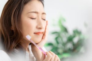 woman with poor brushing habits experiencing dental pain