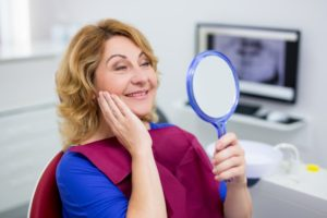 Patient admiring smile after denture to implant transition