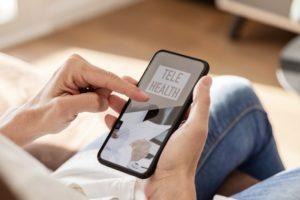 Telehealth on phone, one of the emerging dental trends