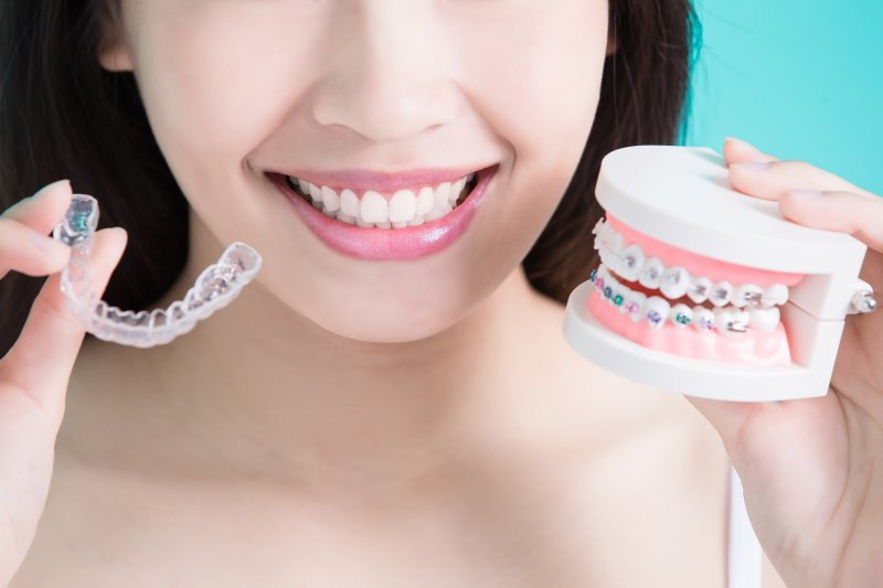 a woman holding a mouth mold with traditional braces as well as a clear Invisalign aligner